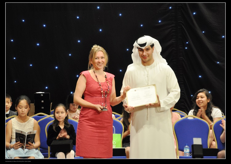 """Yana Welch, Founder of The Music Hub receives an award from a representative of The Ministry of Culture, Youth and Community Development for her Outstanding Achievement as a Teacher for her piano students. Her students won the first and third prizes at the 2nd UAE International Chopin competition."""